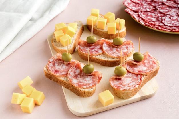 Sandwiches van rookworst en witbrood versierd met groene olijven en kaas op roze papier