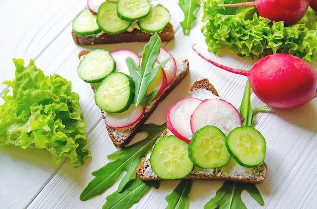 Sandwiches van tarwe bruin brood met komkommers en radijs met bladeren van verse groene salade