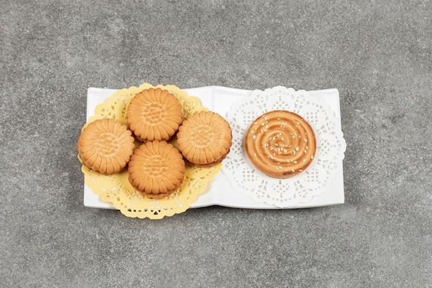 Sandwichkoekjes en koekje met sesamzaadjes op witte plaat