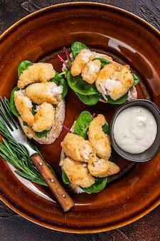 Sandwichs met gebakken garnalen, garnalen, spinazie en snijbiet salade op een rustieke plaat