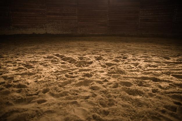 Sandy horse riding arena met lichte plek in het midden