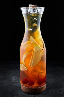 Sangria in een doorzichtige kan met ijs, op een zwarte tafel