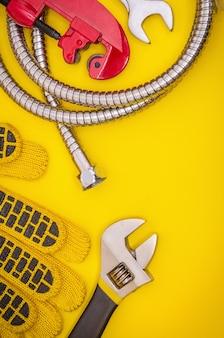 Sanitair gereedschap en handschoenen voor het aansluiten van waterslangen op gele tafel voor werk