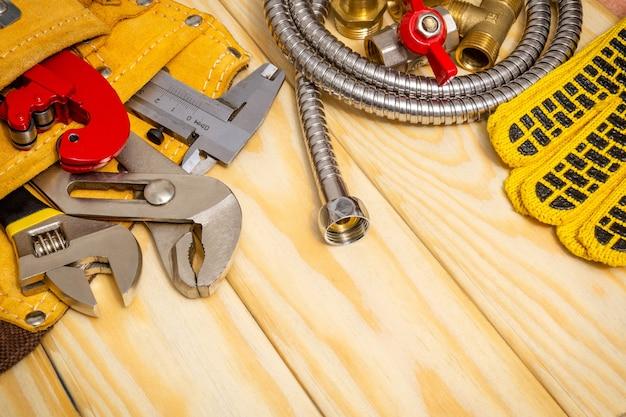 Sanitair gereedschap in de zak en slang op houten planken