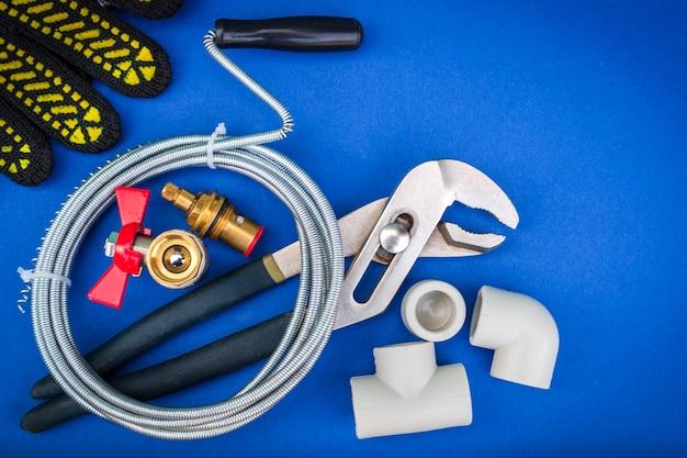 Sanitair gereedschap, kabel en handschoenen voor het aansluiten van waterslangen op blauwe achtergrond