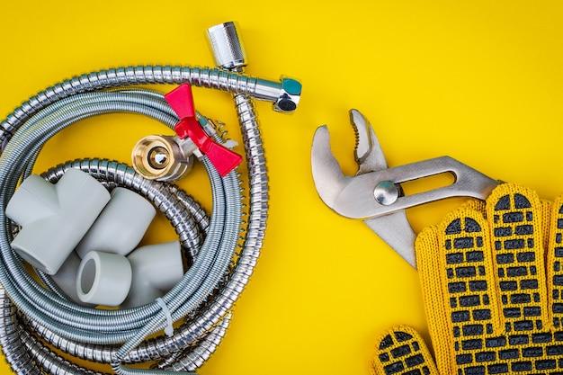 Sanitair gereedschap, kabel en handschoenen voor het aansluiten van waterslangen op gele achtergrond