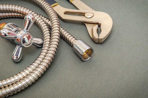 Sanitair materialen kraan, gereedschap en slang op donkergroene ruimte worden gebruikt voor vervanging onder de douche