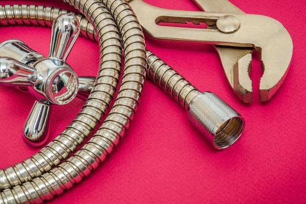 Sanitair materialen kraan, gereedschap en slang op paarse ruimte worden gebruikt voor vervanging onder de douche