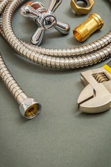 Sanitair materialen kraan, gereedschap, fittingen en slang op donkergroene ruimte worden gebruikt voor vervanging onder de douche