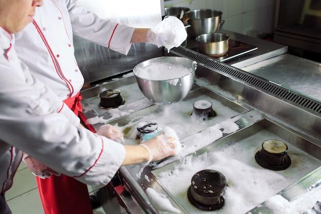 Sanitaire dag in het restaurant. cooks wassen oven, fornuis en afzuigkap in het restaurant.