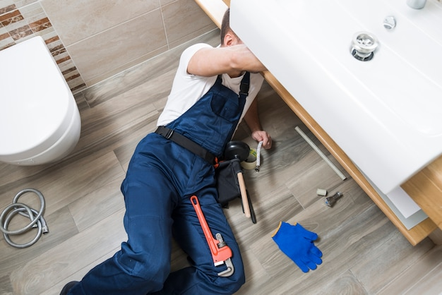 Sanitaire technicus die onder gootsteen werkt