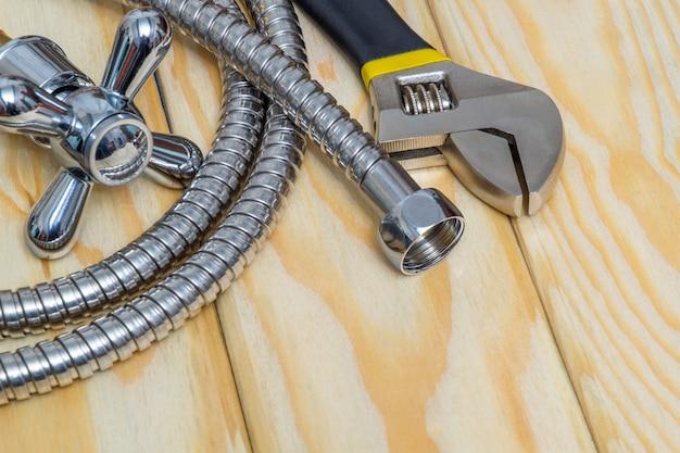 Sanitairgereedschap, materialen, kraan en slang op houten planken worden gebruikt om te vervangen of te repareren