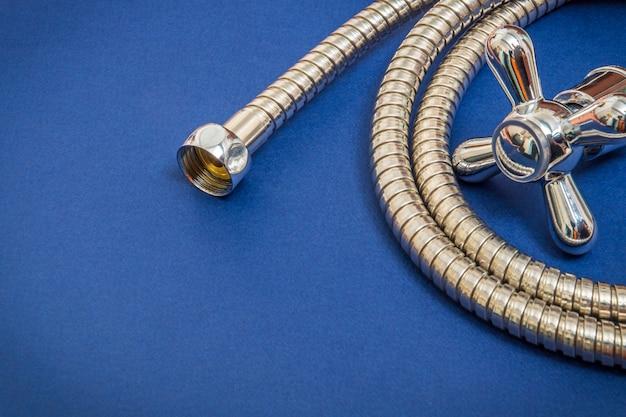 Sanitairmaterialen kraan en slang op blauwe ruimte worden gebruikt voor vervanging onder de douche