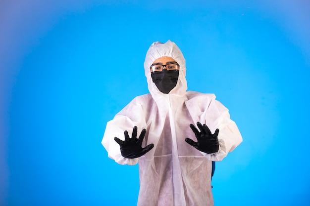 Sanitizer in speciaal preventief uniform en zwarte maskers maakt stopborden met beide handen