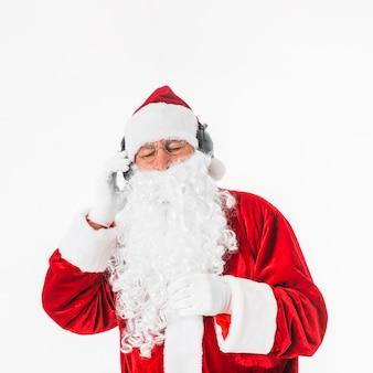 Santa claus die aan muziek met hoofdtelefoons luistert
