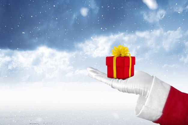 Santa claus die de doos van de kerstmisgift met sneeuwval toont