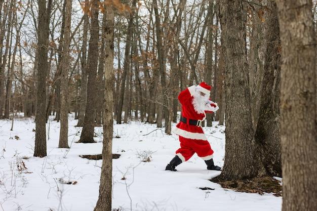 Santa claus die door het winterbos loopt met kerstcadeautjes en wegkijkend