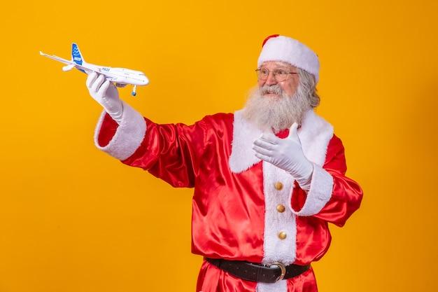 Santa claus die een klein stuk speelgoed vliegtuig op gele achtergrond houdt. kerst reisconcept
