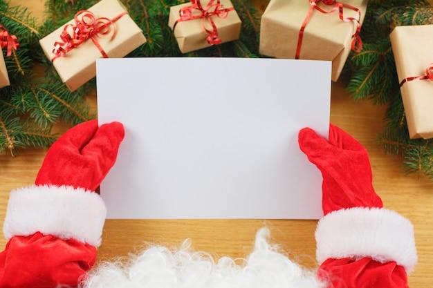 Santa claus die een lege wensenlijst in zijn handen houdt