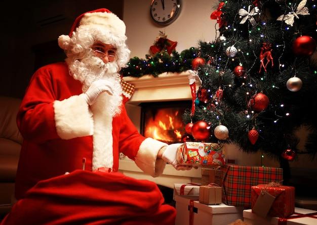 Santa claus die giftdoos of heden onder de kerstboom zet bij vooravond. het is een geheim. verrassing. vertel het niet aan de kinderen. kerst- en nieuwjaarsvakantie