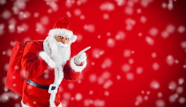 Santa claus die in leeg rood met sneeuw richt