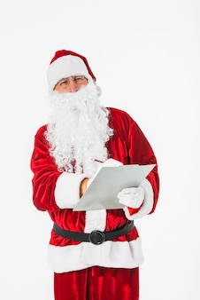 Santa claus die op papier met potlood schrijft