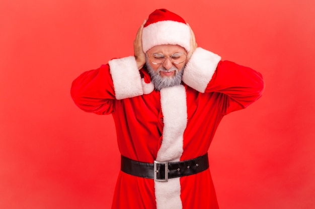 Santa claus die oren bedekt met handpalmen, hard geluid, fronsend gezicht.