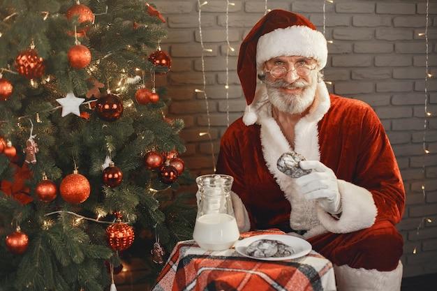 Santa claus die rust bij de kerstboom. huisdecoratie. cadeau voor de kerstman.