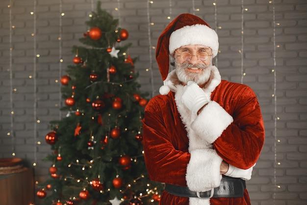 Santa claus die zich bij de kerstboom bevindt. huisdecoratie.