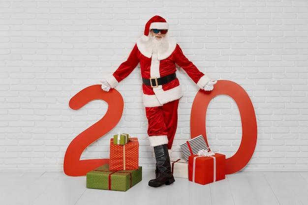 Santa claus die zich dichtbij giftdozen en aantallen van 20 bevindt