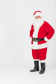 Santa claus die zich met handen op heupen bevindt