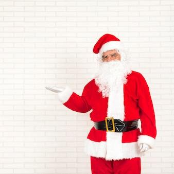 Santa claus die zich met uitgestrekte hand bevindt