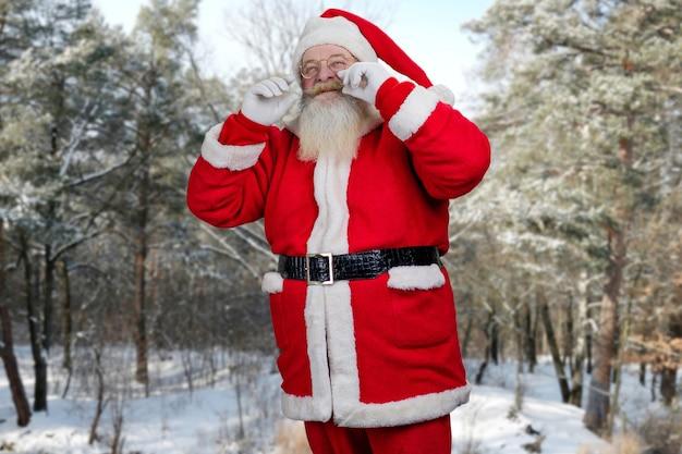 Santa claus die zijn snor aanraakt.