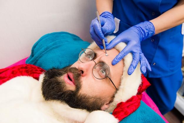 Santa claus doet cosmetische ingrepen in de spa-kliniek. cosmetische ingrepen in kuuroordkliniek