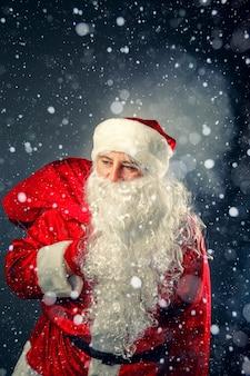 Santa claus draagt geschenken.