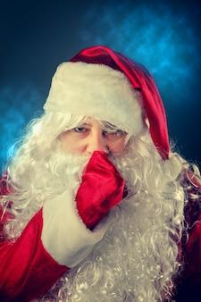 Santa claus drukt een vinger op zijn lippen.
