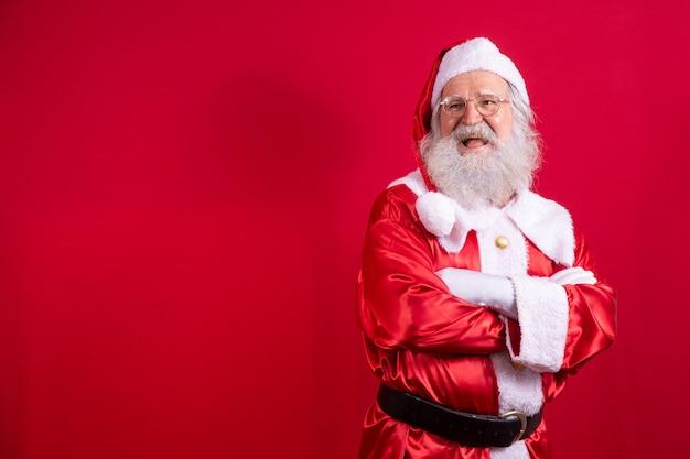 Santa claus gekruiste armen op rode achtergrond. vriendelijke bebaarde kerstman met armen gevouwen over rode achtergrond. studio-opname van de realistische kerstman.