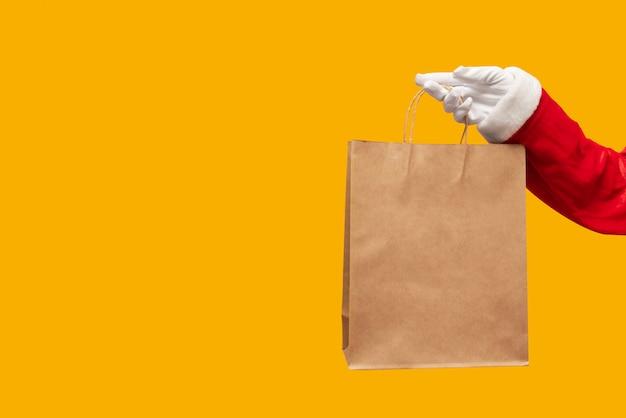 Santa claus-hand die bruine het winkelen zak met over geïsoleerd houden.