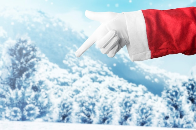 Santa claus-hand die iets met sneeuwval richt