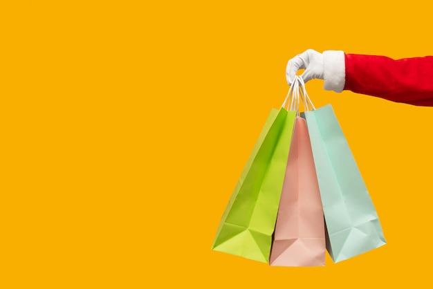 Santa claus-hand die kleurrijke het winkelen zakken op geïsoleerd geel houden.
