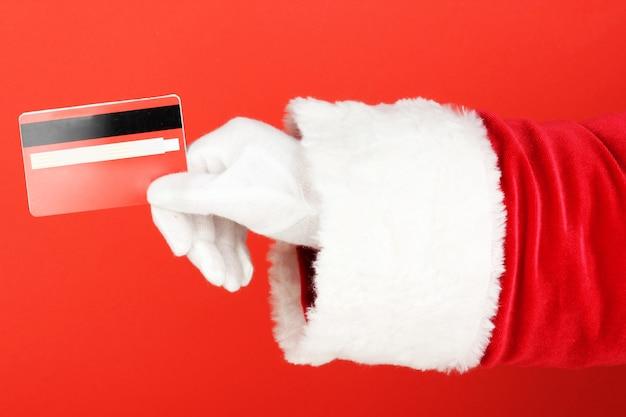 Santa claus-hand die rode creditcard op rode achtergrond houdt