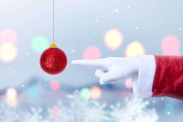 Santa claus-hand die rode kerstmisbal met vage lichte achtergrond richt. vrolijk kerstfeest