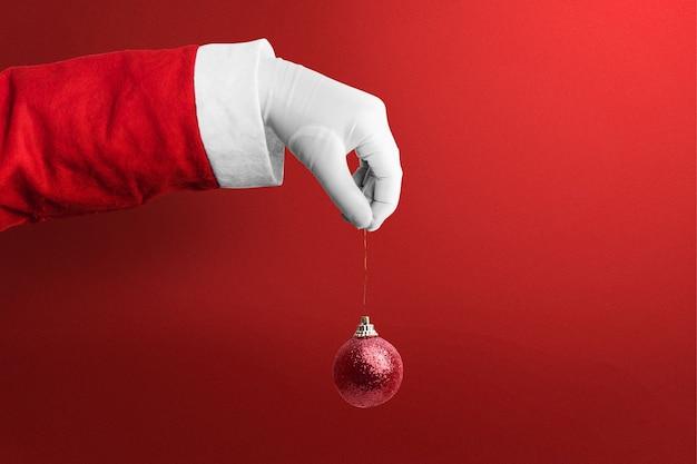 Santa claus hand met kerst versiering met een rode achtergrond. vrolijk kerstfeest
