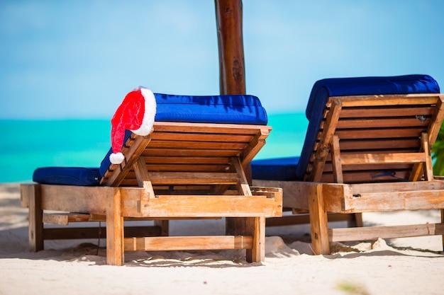 Santa claus hat op strandlanterfanter met turkoois zeewater en wit zand. kerst vakantie concept