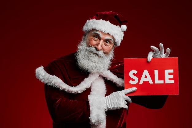 Santa claus holding sale-teken