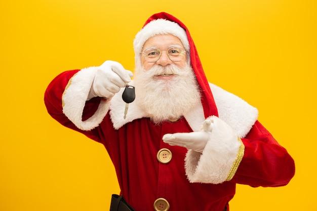 Santa claus-holdingssleutels van een auto op gele achtergrond.