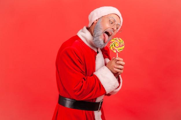 Santa claus houdt in handen suikerachtig snoep, veelkleurige lolly bijten.