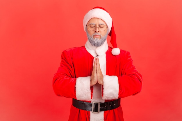 Santa claus houdt namaste gebaar, mediteren, yoga oefening ademtechniek vermindert stress.