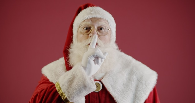 Santa claus houdt wijsvinger bij zijn mond en kijkt naar de camera shh sh