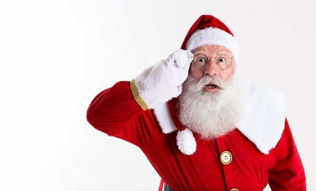 Santa claus in bril kijkt verbaasd naar camera op witte achtergrond